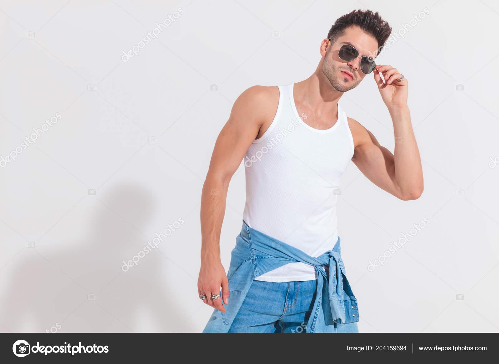 Retrato Jovem Camiseta Consertar Seus Óculos Escuros Enquanto Fundo Branco  — Fotografia de Stock f4641ce6a4