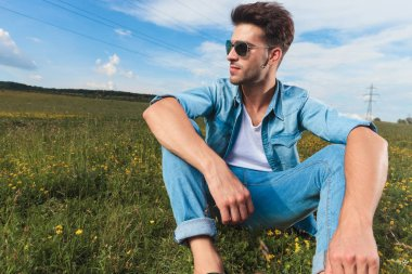 seated casual man with sunglasses and undone denim shirt admires the nature while at the countryside