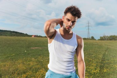 young man in undershirt arranges his hair while standing outside in a grass field