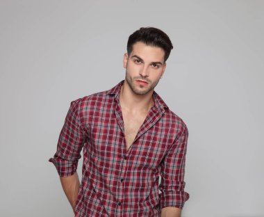 casual young man with open collar shirt is standing on grey background
