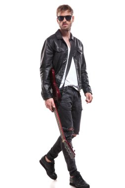 handsome fashion man wearing leather jacket and sunglasses stepping to side while holding guitar on white background
