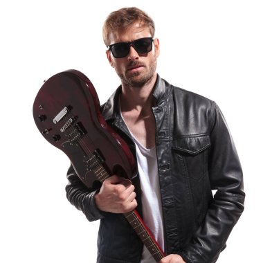 portrait of young rock star wearing sunglasses and leather jacket wanting to smash his electric guitar while standing on white background