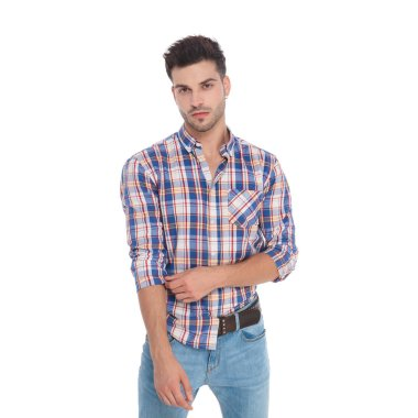 portrait of seductive man fixing his plaid shirt sleeve while standing on white background