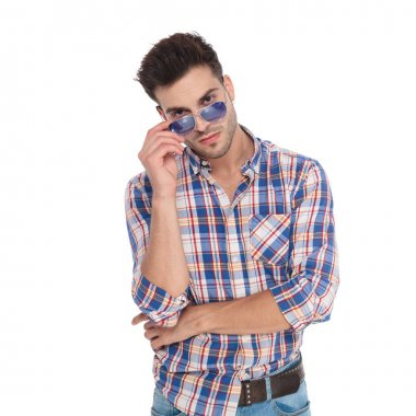 portrait of attractive casual man wearing a shirt with checkers looking over his sunglasses while standing on white background