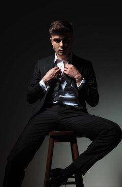 portrait of seductive man in tuxedo fixing his undone bowtie while sitting on wooden chair on grey background