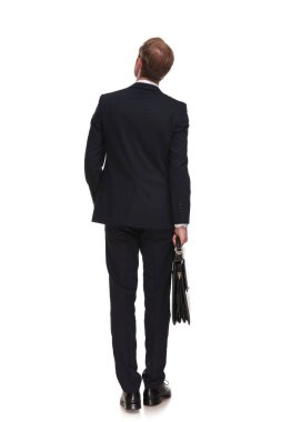 behind of curious businessman with suitcase looking up to side while standing on white background with a hand in pocket, full length picture