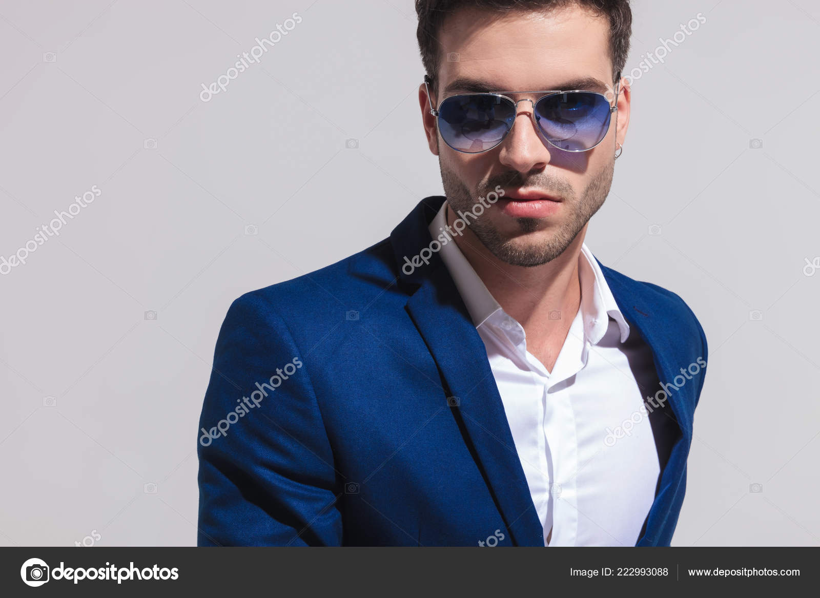 66a0677335de Closeup portrait of a sexy young elegant man in blue suit and sunglasses  looking at tne camera on grey background– stock image