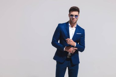 fashion sexy man in suit and sunglasses fixes his sleeve on grey background