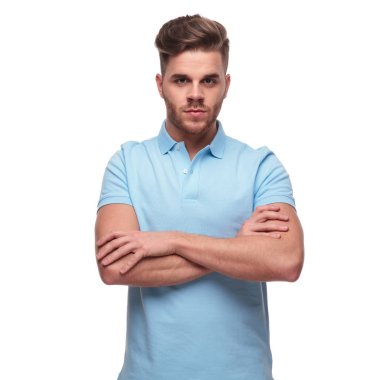 portrait of confident casual man wearing a polo shirt while standing on white background