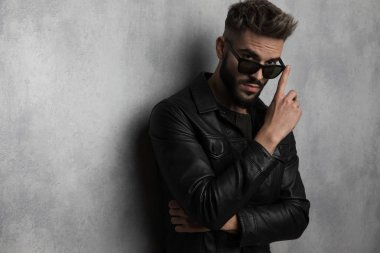 portrait of casual man in leather jacket touching his sunglasses while leaning against a grey wall