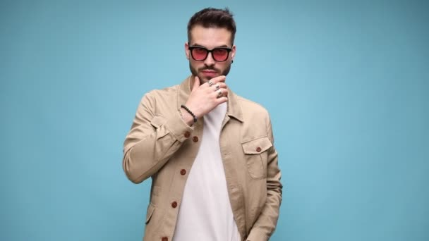 confident young fashion model wearing sunglasses,walking and moving,touching chin and thinking, adjusting coat and holding hands in pockets on blue background