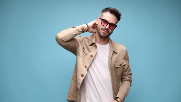 sexy young casual man wearing glasses, holding one hand behind neck and the other one in pocket, watching sensually over glasses, adjusting jacket and moving in a side view position on blue background