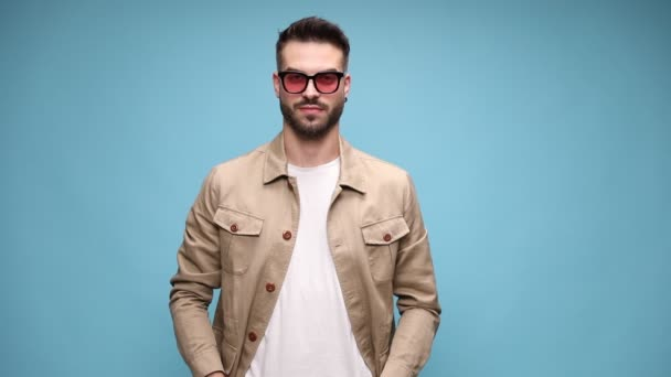 thoughtful young casual man wearing glasses and jacket, crossing arms and smiling, standing on blue background