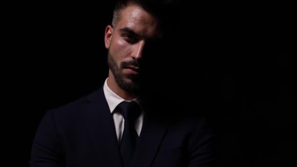 geheimnisvoller junger Geschäftsmann im Anzug steht und posiert im Modelicht, verschränkt die Arme und fixiert Anzug und Krawatte auf dunklem Hintergrund
