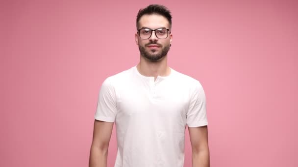 handsome casual man wearing eyeglasses, standing against pink background, crossing his arms to chest and smiling