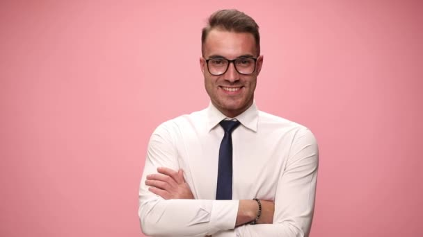 confident young businessman in white shirt smiling crossing arms holding hands in pockets and adjusting glasses on pink background