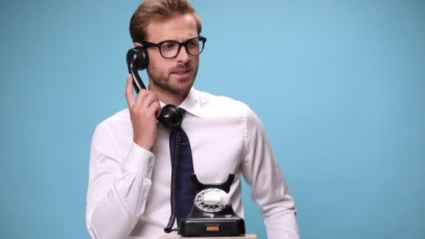vonzó üzletember felveszi egy régi telefont, beszél valakivel, és dühös lesz, vitatkozik és sikoltozik, majd rácsapja a telefont a kék háttér