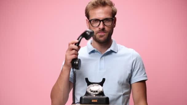 ležérní mladý muž v modré polo košili, mluví do starého telefonu, usmívá se, ukazuje prsty a dělat gesto telefonu na růžovém pozadí