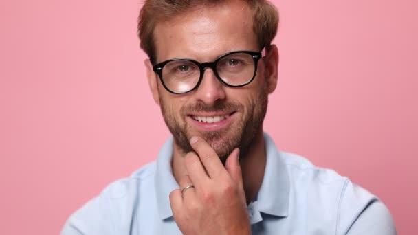 zblízka mladý ležérní chlap v modré polo košile nosí brýle, dotýká bradu a myšlení, dívá se na stranu, usmívá se na růžovém pozadí