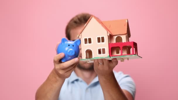 šťastný mladý ležérní chlap v modré polo shirt drží prasátko banky a dům model před obličejem, prezentovat a doporučující, usmívat se na růžovém pozadí