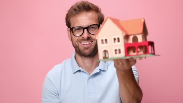 mladý ležérní šťastný muž v modré polo košile ukazuje dům model, usmívat se, dělat palce nahoru znamení a přikyvování na růžovém pozadí