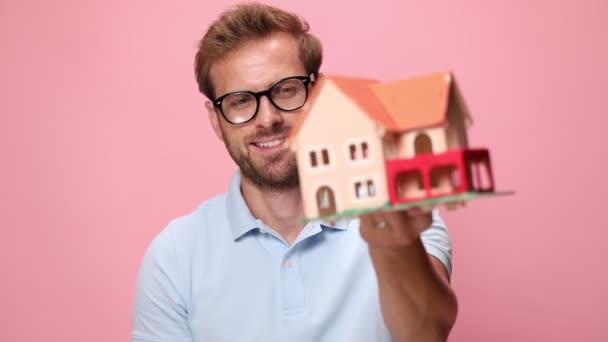 alkalmi fiatal férfi kék pólóban ajánló ház modell, mosolygós, tartsa öklével a levegőben, és ünneplő, nevetés és sikoltozás rózsaszín háttér