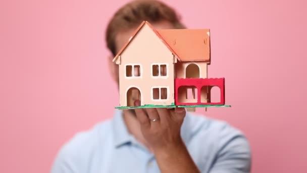 Lächelnder junger, lässiger Mann in blauem Polohemd mit Brille, das Hausmodell vor dem Gesicht, lächelnd und Schlüsselanhänger auf rosa Hintergrund