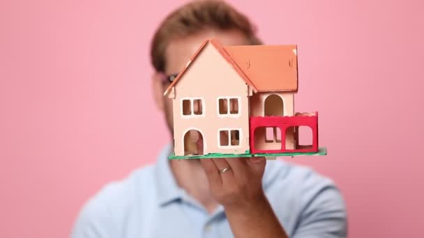 young casual man in blue polo shirt covering face with house model, showing and offering keys on pink background