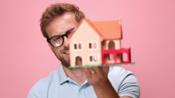 happy young casual man in blue polo shirt holding house model in front of face, recommending and offering keys on pink background