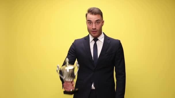 Aufgeregter Geschäftsmann präsentiert seinen Pokal und feiert Erfolge auf gelbem Hintergrund