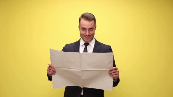 šťastný podnikatel čte noviny, usmívá se a potřásá hlavou na žlutém pozadí