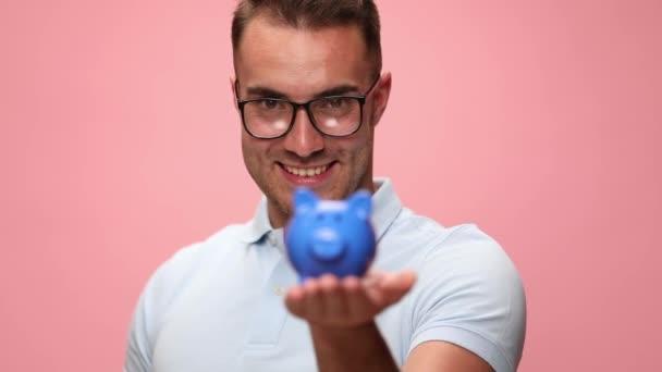 sexy lässiger Mann legt Geld in sein Sparschwein und feiert Erfolge