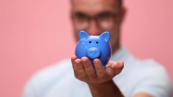 ležérní muž investovat peníze do prasátko banky a dávat palce nahoru