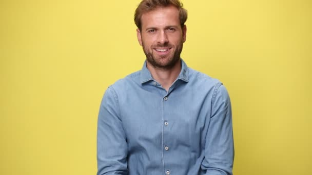 handsome businessman smiling wide, folding his arms and approving on yellow background