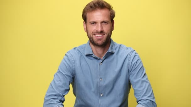 young businessman smiling at the camera, crossing his arms, laughing and having fun on yellow background