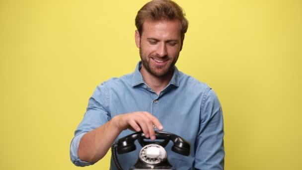 sexy obchodník mluví na retro telefon, směje se a dává palce nahoru na žlutém pozadí