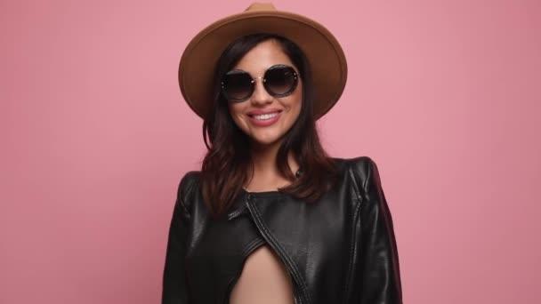 šťastná žena v kožené bundě nosí sluneční brýle a klobouk, usmívá se, aranžuje vlasy, dívá se dolů a pózuje na růžovém pozadí