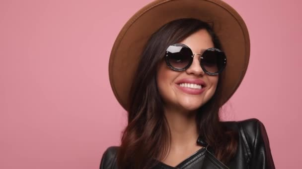 young girl in leather jacket wearing hat and sunglasses smiling, looking to side and posing on pink background