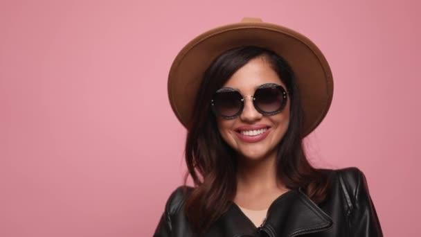 boldog lány bőrdzsekiben visel kalap és napszemüveg futó ujjak a hajat, és rögzíti, látszó oldalra, és mosolyog, pózol a rózsaszín háttér