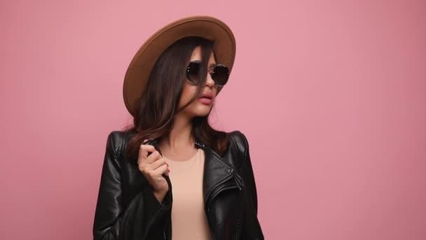 smyslná cool dívka v kožené bundě, nosí klobouk a sluneční brýle, drží bundu, dívá se stranou a pózuje, drží ruce v kapsách na růžovém pozadí