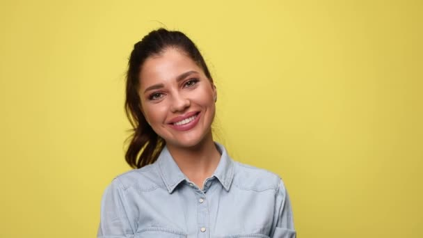 attractive young casual girl in blue denim shirt smiling and posing on yellow background