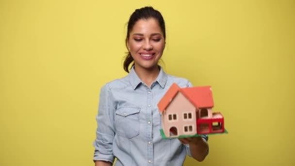 žena v modré džínové košili drží dům model nahoru, prezentuje a doporučuje, usmívá se a ukazuje prstem na žluté pozadí