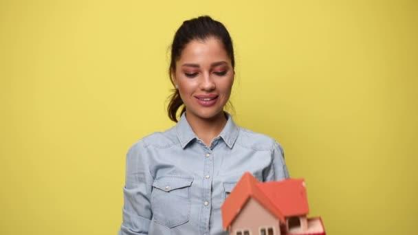 aufgeregtes junges Mädchen hält die Fäuste in die Höhe und feiert den Sieg, präsentiert und empfiehlt das Hausmodell auf gelbem Hintergrund