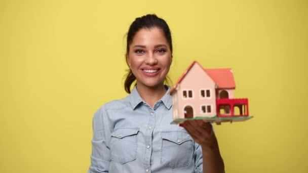 junge lässige Frau in blauem Jeanshemd zeigt und präsentiert Baumodell, zeigt Finger, hält Fäuste in die Luft und jubelt auf gelbem Hintergrund