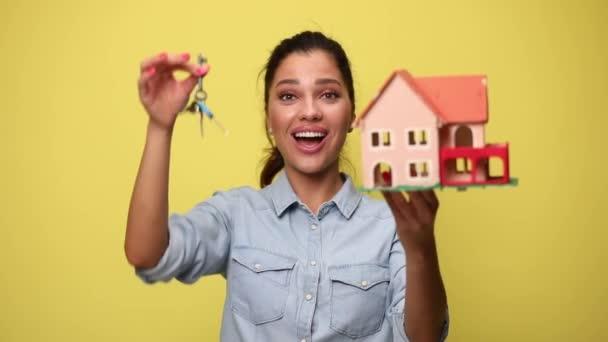lächelnde lässige Frau in blauem Jeanshemd, die Hausmodell und Schlüssel auf gelbem Hintergrund zeigt und präsentiert