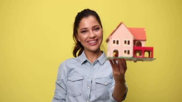 glückliche junge Frau präsentiert und empfiehlt Baumodell, zeigt Schlüssel und lächelt auf gelbem Hintergrund