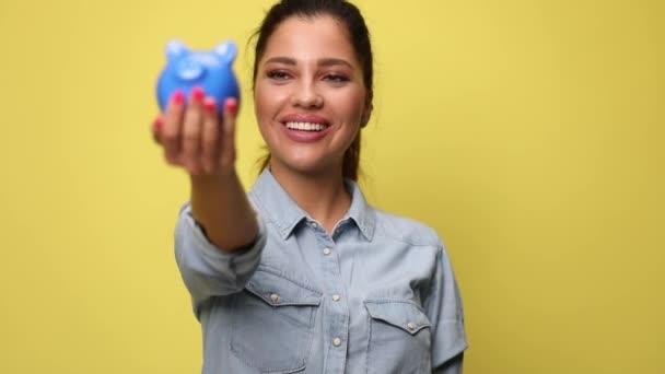 mladá šťastná žena v modré džínové košili představuje a doporučuje prasátko banky a stavební model, usmívá se na žlutém pozadí