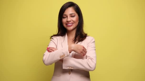 young businesswoman with a large smile on her face is crossing her arms and looking at the camera on yellow background