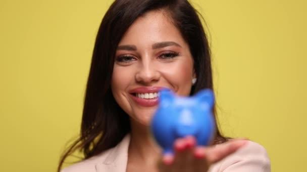 sexy Geschäftsfrau hält ihr Sparschwein und steckt Geld hinein