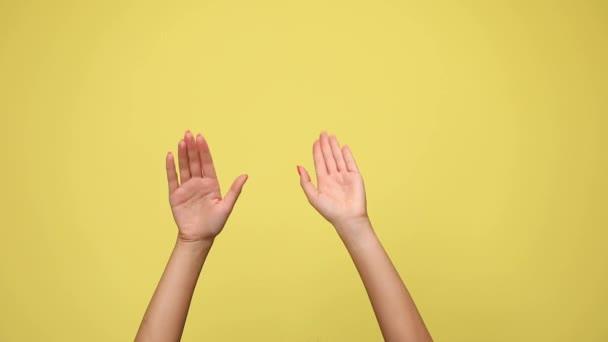 dvě paže se točí dokola, naklánějí, tleskají, tleskají jeden o druhého a dávají palce nahoru proti žlutému pozadí